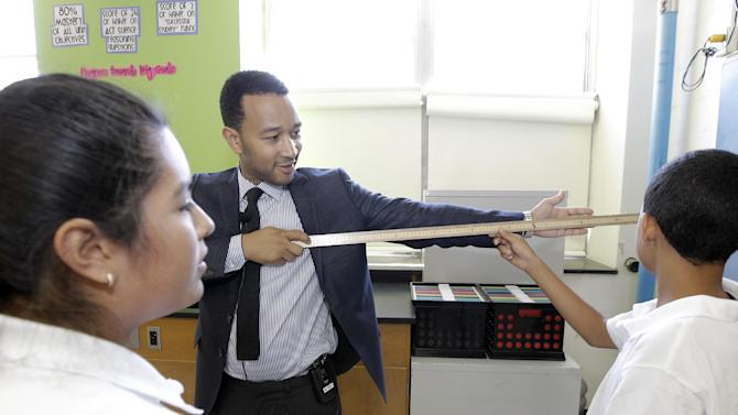 Johana Numez, 12, and Joe Peek,14, help JCP Cares Supporter John Legend measure his 'wing span' during their science class at L.V. Stockton Middle School on Monday Sept. 10,  2012, in Dallas. (Photo by Brandon Wade/Invision for JCPenny /AP Images)