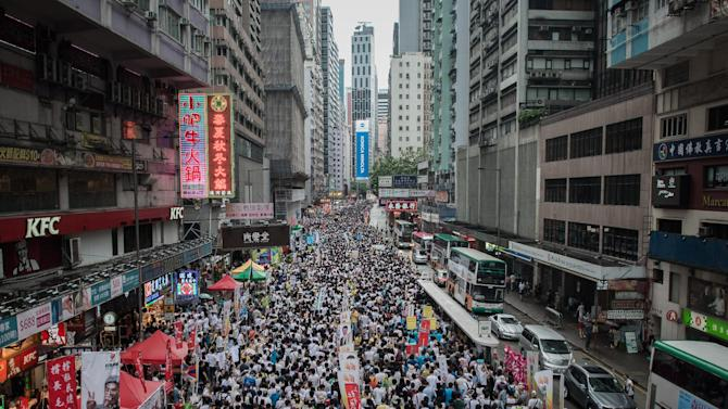 Demonstrators march during a pro-democracy rally in Hong Kong on July 1, 2014 as frustration grows over the influence of Beijing on the city