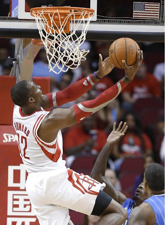 Houston Rockets' Dwight Howard (12) goes to the basket against the Orlando Magic in the first half of an NBA preseason basketball game Wednesday, Oct. 16, 2013, in Houston
