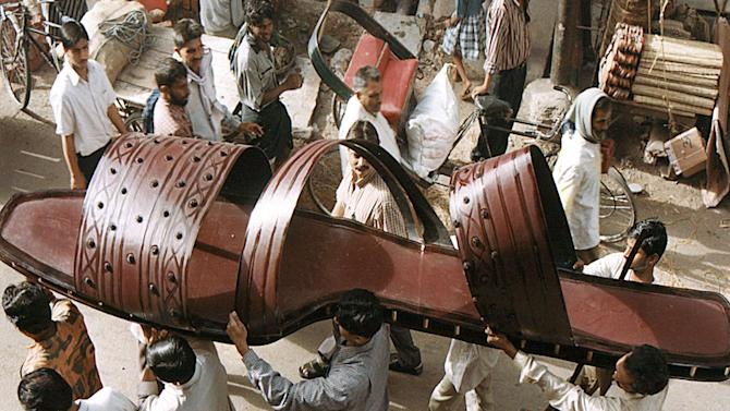 INDIAN WORKERS CARRY A GIANT SLIPPER FOR PUBLIC DISPLAY THROUGH A STREET IN THE NORTHERN INDIAN CITY ...