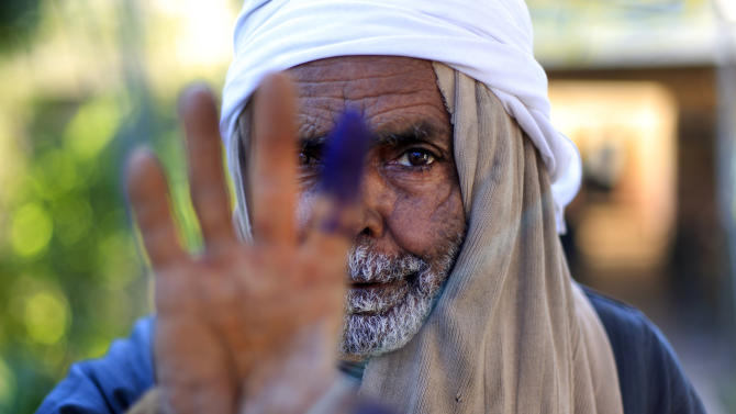 An Egyptian elderly man shows his inked finger after casting his vote on the second round of a referendum on a disputed constitution drafted by Islamist supporters of President Mohammed Morsi in Fayoum, about 100 kilometers (62 miles) south of Cairo , Egypt, Saturday, Dec. 22, 2012.(AP Photo/Khalil Hamra)