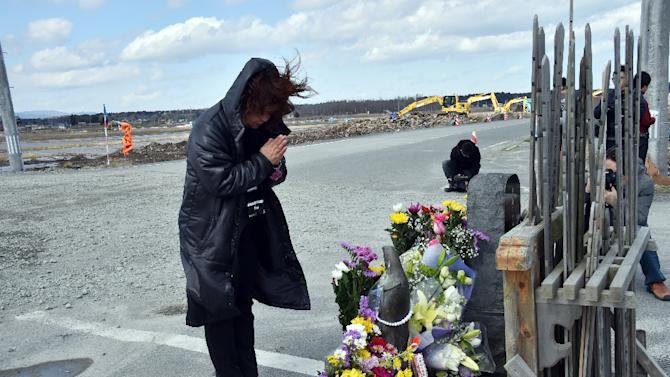 A woman offers a prayer at the altar at Namie, near the striken TEPCO's Fukushima Dai-ichi nuclear plant in Fukushima prefecture on March 11, 2015 on the fourth anniversary day of a massive earthquake and tsunami that hit northern Japan