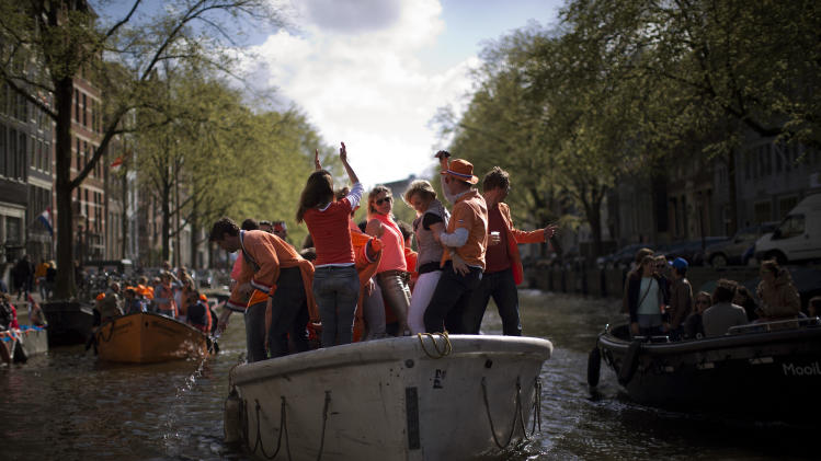 People celebrate dancing In their boats as they sail along a canal in Amsterdam, The Netherlands, Tuesday April 30, 2013. Around a million people are expected to descend on the Dutch capital for a huge street party to celebrate the first new Dutch monarch in 33 years. (AP Photo/Emilio Morenatti)