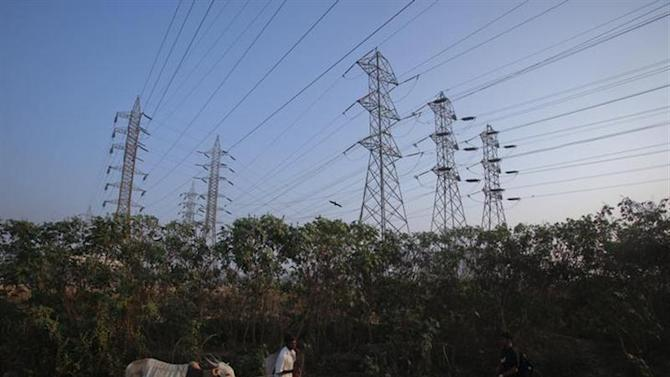 A man walks his cow under high-tension power lines leading from a Tata Power sub station in Mumbai's suburbs February 10, 2013. REUTERS/Vivek Prakash/Files