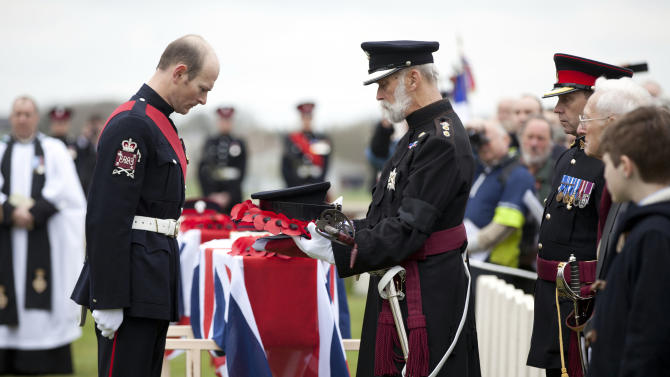 A poppy wreath and sword of Lieutenant John Harold Pritchard are handed to Prince Michael of Kent, center right, during a ceremony at the H.A.C. cemetery in Ecoust-St-Mein, France on Tuesday, April 23, 2013. Almost 100 years after they were killed in action, Lieutenant John Harold Pritchard and Private Christopher Douglas Elphick were re-interred with full military honors in a private ceremony. Lieutenant Pritchard was killed in action on May 15, 1917 during an enemy attack near Bullecourt, France and his remains were found in a field near the site in 2009. His body was eventually identified by a silver bracelet with his name engraved on it. Private Elphick was born in Dulwich, South London in 1889. He was killed in action on May 15, 1917 during an enemy attack near Bullecourt, France and his remains were found in a field near the site in 2009. His body was eventually identified by a signet ring bearing his initials. (AP Photo/Virginia Mayo)