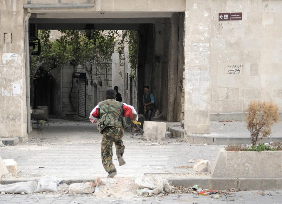 In this Tuesday, Nov. 6, 2012 photo, a Syrian rebel runs for cover to avoid Syrian Army sniper fire on Sabaa al- Bahriat street, in the Old City of Aleppo, Syria.(AP Photo/Monica Prieto)