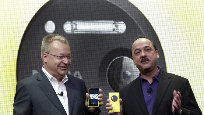 Nokia CEO Stephen Elop, left, and AT&T Mobility CEO Ralph de la Vega talk about the Nokia Lumia 1020 during its introduction, in New York, Thursday, July 11, 2013. The Nokia Lumia 1020, with a 41-megapixel camera, records more detail than other camera phones and even tops point-and-shoot cameras. (AP Photo/Richard Drew)
