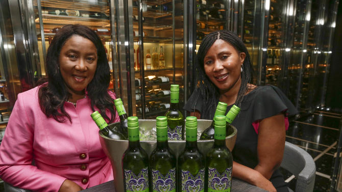 "FILE : In this image taken on Thursday, Feb. 21, 2013, former South African president Nelson Mandela's daughter, Makaziwe Mandela, left, and his granddaughter Tukwini Mandela pose with some of their House of Mandela wines, in Bal Harbour, Fla. For decades, Nelson Mandela's name has been synonymous with freedom and political reform. Now with the launch of House of Mandela Wines, his daughter and granddaughter hope to add fine wine to the list of associations. Perhaps not surprisingly, the Mandela name is also being used commercially by members of his family. There is a ""House of Mandela"" wine label and two granddaughters are starring in a U.S. television reality show titled ""Being Mandela."" Mandela, old and frail, lives in seclusion in his Johannesburg home. Beyond the high walls of the house, the fighting over his image and what he stood for has already begun. (AP Photo/Wilfredo Lee)"