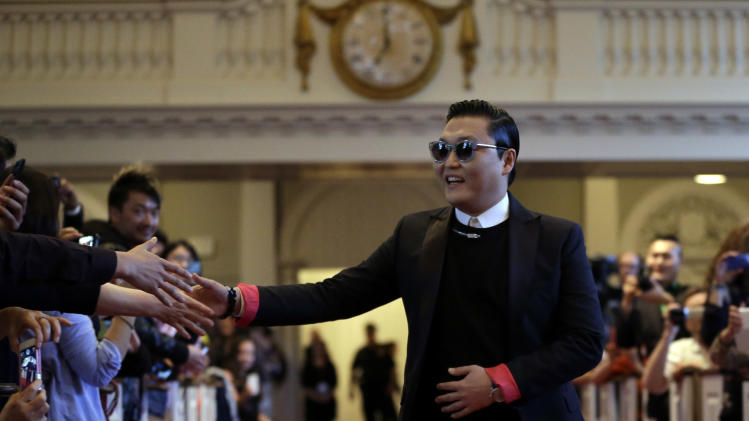 Korean pop star PSY arrives in Memorial Church to speak at Harvard University in Cambridge, Mass., Thursday, May 9, 2013. Dozens of screaming and shouting Harvard University students have welcomed South Korean pop star PSY for a conversation inside an ornate church dedicated to the memory of those who lost their lives in World War I. (AP Photo/Elise Amendola)