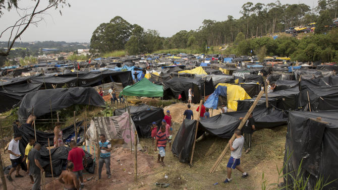 Members of the Homeless Workers Movement build their shacks on occupied land within view of Itaquerao stadium in Sao Paulo, Brazil, Tuesday, May 6, 2014. Thousands of impoverished Brazilians have squatted near the World Cup stadium hosting the opening match of soccer's biggest tournament, saying the arena's construction is to blame for rent increases that drove them out of their homes. (AP Photo/Andre Penner)