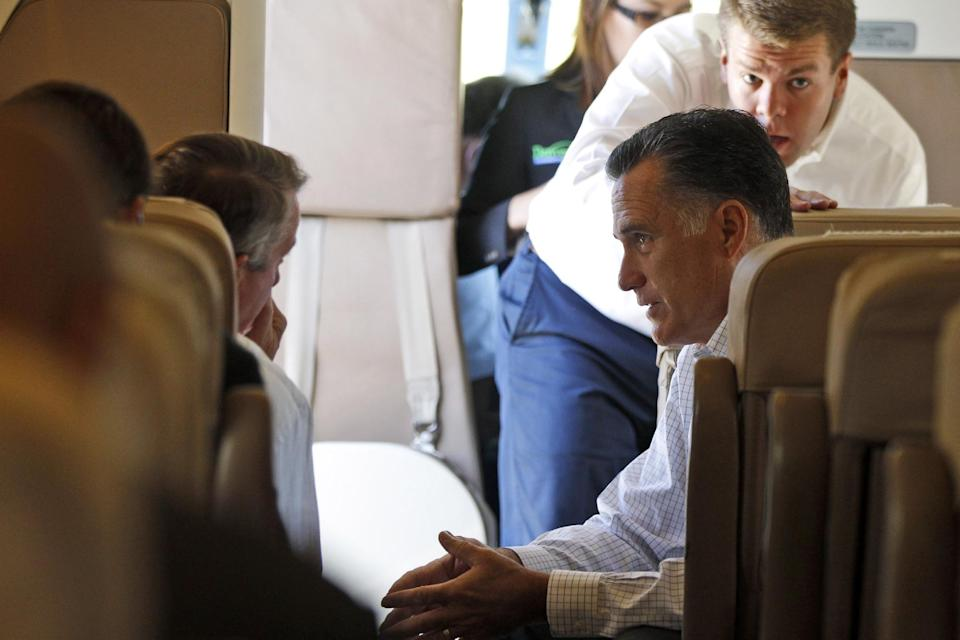 Republican presidential candidate, former Massachusetts Gov. Mitt Romney speaks with senior advisor Ed Gillespie, left, as aide Garrett Jackson stands at right after they boarded their campaign charter plane in Aspen, Colo., Friday, Aug. 3, 2012, en route to Las Vegas, Nev. (AP Photo/Charles Dharapak)