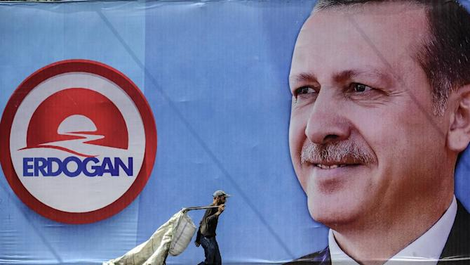 A man collecting rubbish walks past a giant campaign poster of Turkish Prime Minister Recep Tayyip Erdogan on display in Istanbul, on August 8, 2014