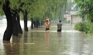 People walk down a flooded road in Anju city in North Korea's South Phongan province. North Koreans hit by recent deadly floods badly need drinking water, food and medical assistance, the Red Cross says