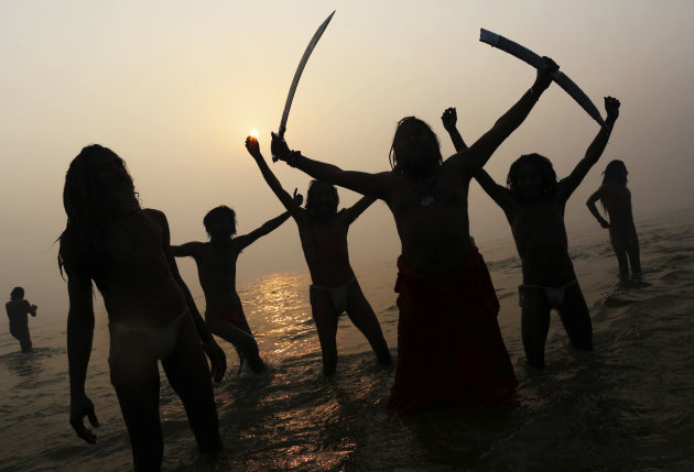 Indian Hindu holy men, or Sadhus, are silhouetted as they celebrate in the water at Sangam, the confluence of the rivers Ganges, Yamuna and mythical Saraswati, during the royal bath on Makar Sankranti