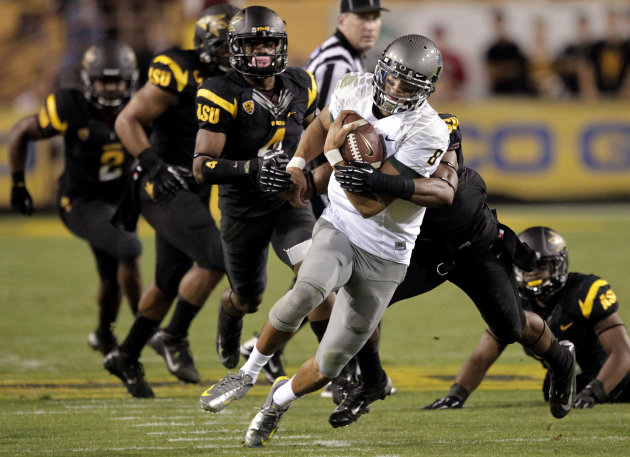 Oregon quarterback Marcus Mariota (8) scrambles for yardage as he is pursued by Arizona State defenders during the first half of an NCAA college football game, Thursday, Oct. 18, 2012, in Tempe, Ariz. (AP Photo/Matt York)