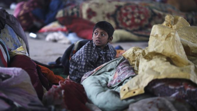 Boy sits under a quilt at a temporary shelter under a flyover on a cold winter morning in New Delhi