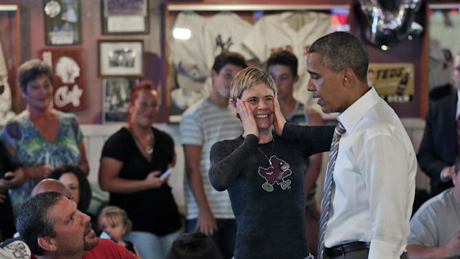 A local patron reacts to seeing President Barack Obama during his unannounced visit at Bob Roe's Point After Pizza, Saturday, Sept. 1, 2012, in Sioux City, Iowa. (AP Photo/Pablo Martinez Monsivais)