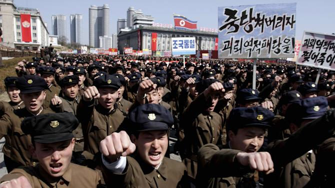 """University students punch the air as they march through Kim Il Sung Square in downtown Pyongyang, North Korea, Friday, March 29, 2013. Tens of thousands of North Koreans turned out for the mass rally at the main square in Pyongyang in support of their leader Kim Jong Un's call to arms. Placards read: """"Let's crush the puppet traitor group"""" and """"Let's rip the puppet traitors to death!"""" (AP Photo/Jon Chol Jin)"""