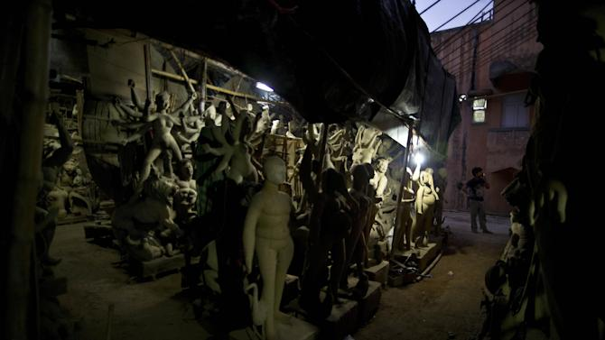 An Indian artist smokes as he takes a break while preparing idols of Hindu goddess Durga ahead of the Durga Puja festival in New Delhi, India, Tuesday, Sept. 16, 2014. During this festival,  the goddess is worshipped for her mythological victory over the evil forces. (AP Photo/Saurabh Das)