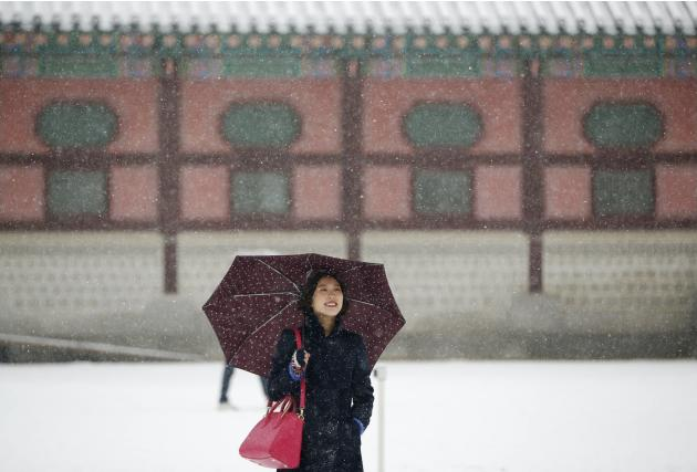 A woman poses for photographs for a friend during snowfall in winter at Gyeongbok Palace in central Seoul