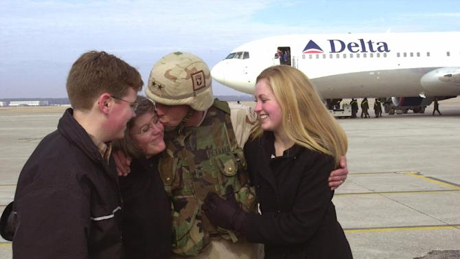FILE - In this Feb. 14, 2004 file photo, Maj. Gen. David Petraeus, center, commanding general of the 101st Airborne Division, kisses his wife, Holly, second left, as his son, Stephen, left, and daughter, Anne, right,  look on upon his return home from Iraq to Fort Campbell, Ky. Gen. Petraeus, the retired four-star general who led the U.S. military campaigns in Iraq and Afghanistan, resigned Friday, Nov. 9, 2012 as director of the CIA after admitting he had an extramarital affair. (AP Photo/Christopher Berkey, File)