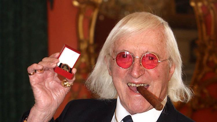 FILE - This is a  March 25, 2008 file photo of Sir Jimmy Savile.  For decades, Jimmy Savile was a fixture on British television — an eccentric, aggressively jocular host of children's shows and a tireless charity fundraiser. A year after he died, aged 84 and honored as Sir Jimmy, several women have come forward to claim he was also a sexual predator and serial abuser of underage girls. The allegations have set off ripples of shock — but not of surprise. There had, colleagues said, long been rumors. The main question being asked now is: Why did no one do anything? (AP Photo/ Lewis Whyld/PA, File)