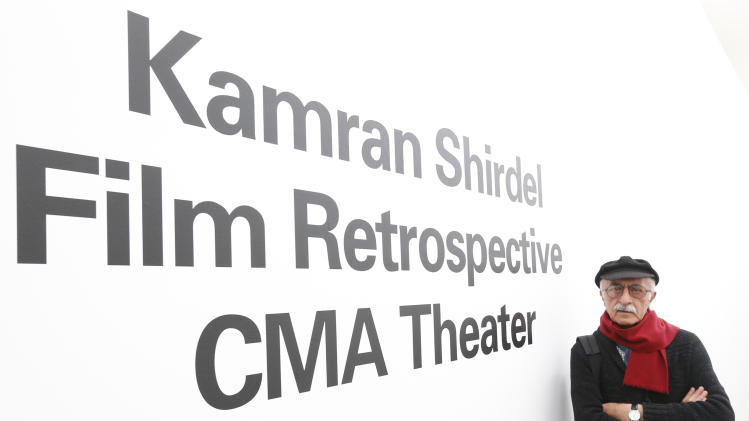 Iranian filmmaker Kamran Shirdel poses beside the sign pointing to where some of his films can be seen at the Carnegie Museum of Art Thursday, Feb. 20, 2014, during his first visit to the U.S. Shirdel began making gritty films of taboo subjects in the 1960s. (AP Photo/Keith Srakocic)