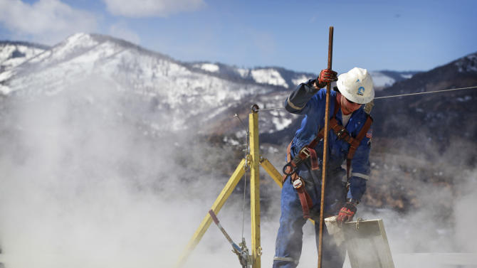 "In this March 29, 2013 photo, a worker checks a dipstick to check water levels and temperatures in a series of tanks at an Encana Oil & Gas (USA) Inc. hydraulic fracturing operation at a gas drilling site outside Rifle, Colorado. Hydraulic fracturing, or ""fracking,"" can greatly increase the productivity of an oil or gas well by splitting open rock with water, fine sand and lubricants pumped underground at high pressure. Companies typically need several million gallons of water to frack a single well. In western Colorado, Encana says it recycles over 95 percent of the water it uses for fracking to save money and limit use of local water supplies. (AP Photo/Brennan Linsley)"