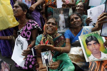 Tamil women cry as they hold up images of their disappeared family members during the war against Liberation Tigers of Tamil Eelam (LTTE) at a protest in Jaffna