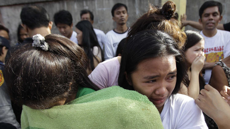 Neighbors and friends cry as they watch firemen retrieve bodies after a fire hit a row of apartments in suburban Quezon City, north of Manila, Philippines on Christmas day Tuesday Dec. 25, 2012. Fire Officer 3 Francisco Mabunga said about 6 people died when a row of houses went up in flames early Christmas day Tuesday. Another fire hit a slum area in San Juan city leaving some 2,000 families homeless. (AP Photo/Aaron Favila)
