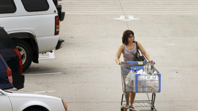 In this photo taken Aug. 25, 2011, a woman pushes a cart in the parking lot of a Little Rock, Ark., Wal-Mart store. Consumer spending rose 0.8 pct. in July, rebounding after first decline in 20 months.  (AP Photo/Danny Johnston)