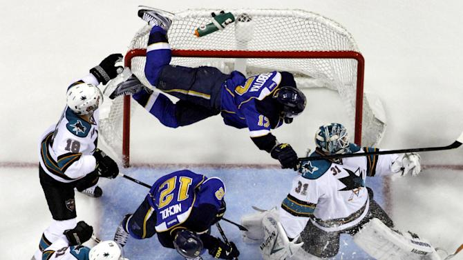 St. Louis Blues' Vladimir Sobotka, top, of the Czech Republic, goes flying into the goal over San Jose Sharks goalie Antti Niemi, right, of Finland, and Blues' Scott Nichol (12) as Sharks' Dominic Moore (18) and Justin Braun (61) watch during the second period in Game 2 of an NHL Stanley Cup first-round hockey playoff series Saturday, April 14, 2012, in St. Louis. (AP Photo/Jeff Roberson)