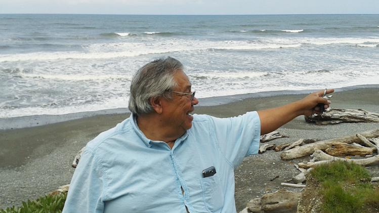 In this photo taken May 28, 2014, James DeLaCruz, an elder with the Quinault Indian Tribe, stands on the Pacific coast of Washington state, near the Quinault village of Taholah. The Corps of Engineers made emergency repairs to the storm-damaged seawall that protects the village in March, 2014, but DeLaCruz says he's worried that the village would still be among the first to go in the case of a tsunami. (AP Photo/Doug Esser)