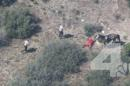 In this frame from video provided by KNBC-TV, officers near a man Thursday, April 9, 2015, near Apple Valley, Calif. A Southern California sheriff on Thursday ordered an immediate investigation after deputies were recorded beating and kicking a man who fled in a car and on horseback. (AP Photo/KNBC-TV) MANDATORY CREDIT