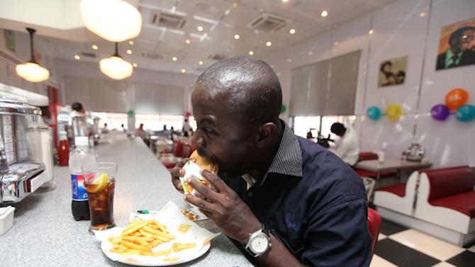 In this photo taken Wednesday, Jan. 23, 2013 Rotimi Fagbemi eats his  hamburger  and fries at Johnny Rockets restaurant in Lagos, Nigeria. As Nigeria's middle class grows along with the appetite for foreign brands in Africa's most populous nation, more foreign restaurants and lifestyle companies are entering the country. And the draw on Nigerians' new discretionary spending has also put new expectations on providing quality service in a nation where many have grown accustomed to expecting very little. ( AP Photo/Sunday Alamba)