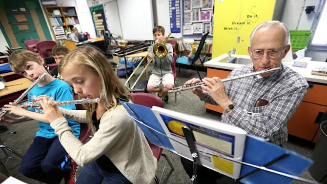 Tony Boland, 79, plays flute during band practice at Kennedy Elementary School Thursday, April 10, 2014, in Dubuque, Iowa. Boland is a volunteer at the school who practices and plays with the school's band. (AP Photo/Telegraph Herald, Jessica Reilly)