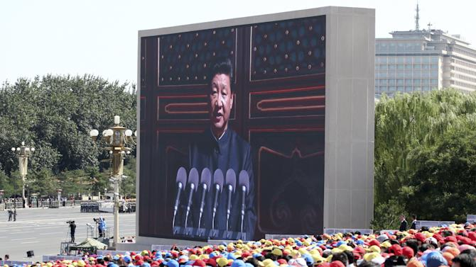 Spectators look on as an electronic screen shows China's President Xi Jinping delivering a speech at the beginning of the military parade marking the 70th anniversary of the end of World War Two, in Beijing