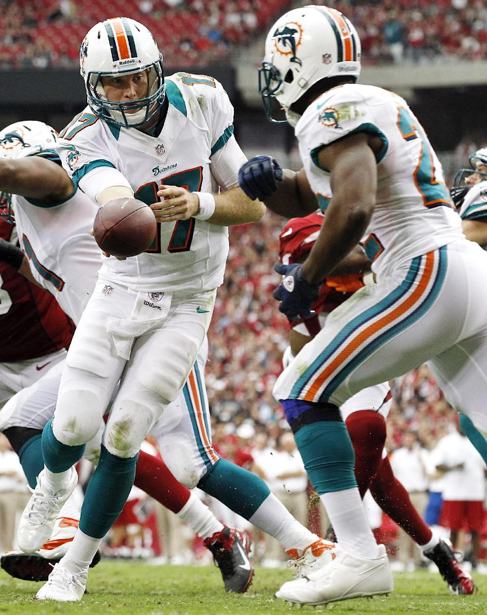 Miami Dolphins quarterback Ryan Tannehill, left, hands off to running back Reggie Bush in the first half of an NFL football game against the Arizona Cardinals, Sunday, Sept. 30, 2012, in Glendale, Ariz. (AP Photo/Ross D. Franklin)