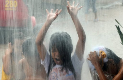 Children are seen playing in rain water pouring from an overflowing roof gutter in Manila, on July 20. One person was missing as heavy rains inundated parts of Manila and nearby areas with knee-deep floodwaters on Saturday, according to the authorities