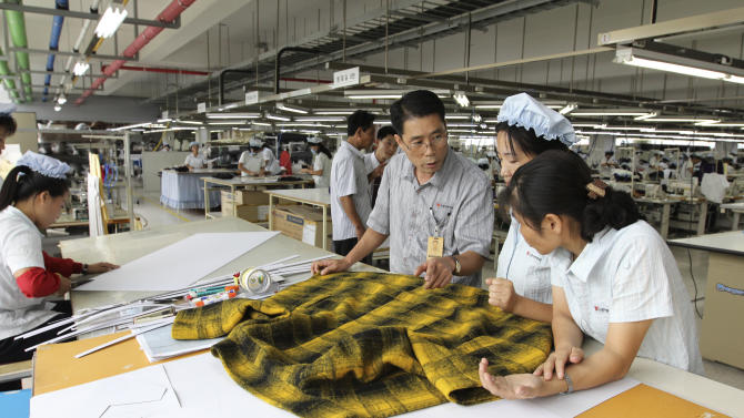 In this Sept. 21, 2012 photo, a South Korean manager consults with North Korean workers preparing to produce clothing at the South Korean-run ShinWon Corp. garment factory inside the Kaesong industrial complex in Kaesong, North Korea. On Wednesday, April 3, 2013, North Korea refused entry to South Koreans trying to cross the Demilitarized Zone to get to their jobs managing factories in the North Korean city of Kaesong. Pyongyang had threatened in recent days to close the border in anger over South Korea's support of U.N. sanctions punishing North Korea for conducting a nuclear test in February. (AP Photo/Jean H. Lee)
