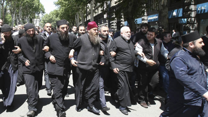 Georgian church clergymen and activists unite to protest against a gay pride rally in Tbilisi, Georgia, Friday, May 17, 2013. Thousands of anti-gay protesters, including Orthodox priests, occupied a central street in Georgia's capital Friday, with some threatening to lash with nettles any participant in a gay pride parade which was to take place there. Police in Tbilisi guarded several dozen gay activists and bused them out of the city center shortly after they arrived at the gathering. (AP Photo/Shakh Aivazov)