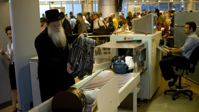 FILE - In this Nov. 2, 2010 file photo, passengers have their hand luggage screened by security personnel inside the Ben Gurion airport terminal near Tel Aviv, Israel. While standing in long lines, walking through scanners and removing belts and shoes are a fact of post 9/11 travel world-wide, Israel's Ben-Gurion Airport seems to stand alone with its security techniques, often leaving travelers dumbfounded by the treatment they have experienced. (AP Photo/Ariel Schalit, File)