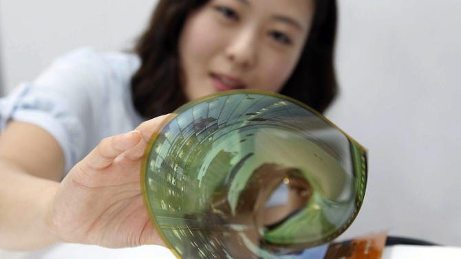 In this July 9, 2014 photo released by LG Display Co., an employee at the company demonstrates an 18-inch flexible display, in Seoul, South Korea. The South Korean display panel maker said Friday, July 11, 2014 it has developed the 18-inch flexible display that can be rolled into the shape of a thin cylinder, a step closer to making a large-size display for flexible TVs. (AP Photo/LG Display Co.)