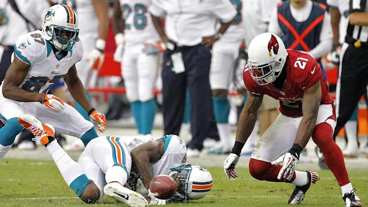 Arizona Cardinals cornerback Patrick Peterson (21) picks up a fumble by Miami Dolphins wide receiver Legedu Naanee during the second half of an NFL football game, Sunday, Sept. 30, 2012,in Glendale, Ariz. The Cardinals won 24-21 in overtime. (AP Photo/Matt York)