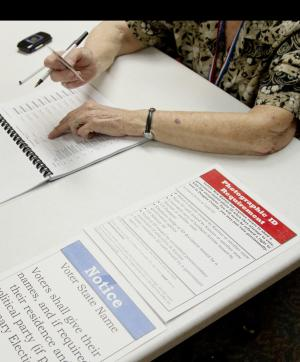 A poll worker checks the identification of a voter in Lawrence, Kan., Tuesday, Aug. 7, 2012. Republican primary voters in Kansas could reshape the Legislature on Tuesday, with conservatives hoping to oust moderate GOP incumbents in the Senate who have stymied the right's political agenda. (AP Photo/Orlin Wagner)