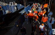 Runners board the Staten Island Ferry in New York, Sunday, Nov. 4, 2012. With the cancellation of the New York Marathon, hundreds of runners, wearing their marathon shirts and backpacks full of supplies, took the ferry to hard-hit Staten Island and ran to neighborhoods hard hit by Superstorm Sandy to help. (AP Photo/Craig Ruttle)