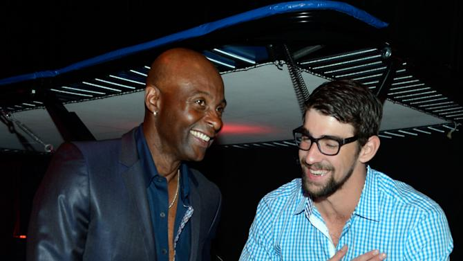 From left, retired Hall of Fame National Football League player Jerry Rice and former U.S. Olympic swimmer Michael Phelps attend the Michael Jordan Celebrity Invitational opening night dinner, Wednesday, April, 3, 2013 in Las Vegas. (Photo by Jeff Bottari/Invision for Jordan/AP Images)