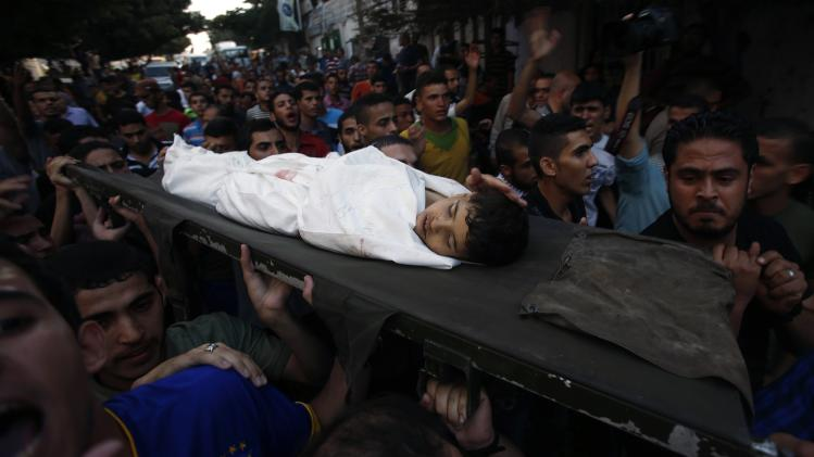 Palestinians carry the body of a boy who was killed in an explosion, during his funeral at Shati refugee camp in Gaza City