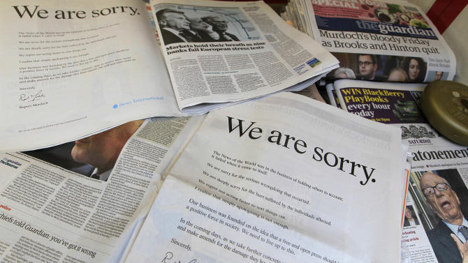 """Newspapers are opened to show the advertisement apology for News International and photographed at a news vendor in central London, Saturday, July 16, 2011.  News Corporation chairman Rupert Murdoch signed the company advert entitled """"We are sorry"""",  which is published in British national newspapers Saturday.  The News International publication News of the World is accused of hacking into the mobile phones of various crime victims, celebrities and politicians. (AP Photo/Sang Tan)"""
