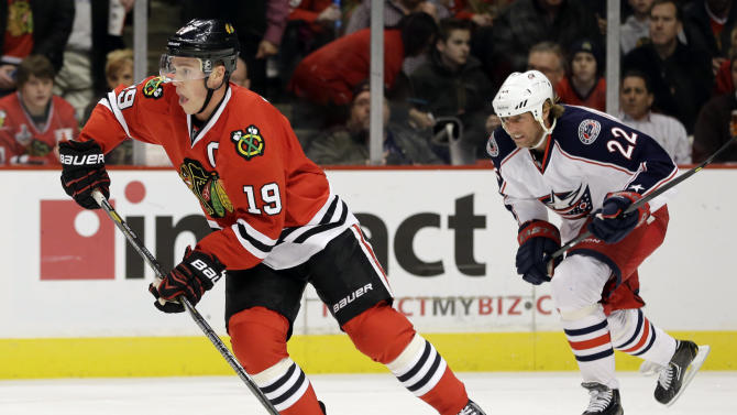 Chicago Blackhawks' Jonathan Toews, left, controls the puck past Columbus Blue Jackets' Vinny Prospal during the first period of an NHL hockey game in Chicago, Friday, March 1, 2013. (AP Photo/Nam Y. Huh)